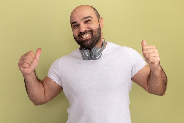 행복하고 밝은 녹색 벽 위에 서 엄지 손가락을 보여주는 헤드폰 흰색 티셔츠에 수염 난된 남자