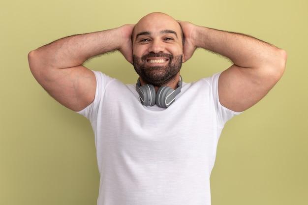 녹색 벽 위에 서있는 그의 머리 뒤에 손으로 행복하고 쾌활한 헤드폰 흰색 티셔츠에 수염 난된 남자