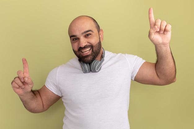 緑の壁の上に立って人差し指で元気に指して幸せで前向きな笑顔のヘッドフォンと白いtシャツのひげを生やした男