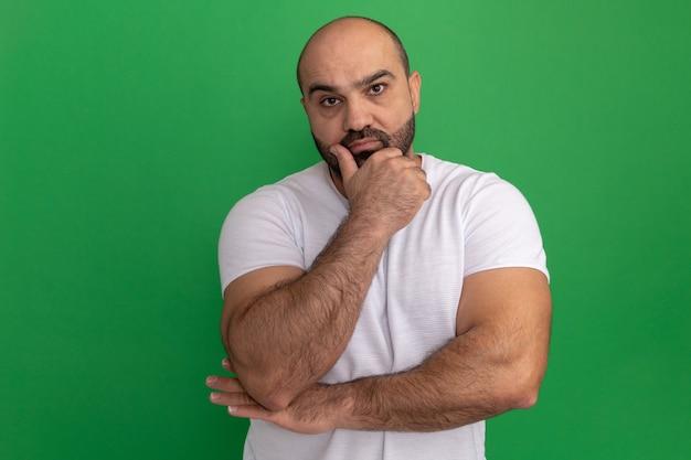 Бородатый мужчина в белой футболке с задумчивым выражением лица думает, стоя над зеленой стеной