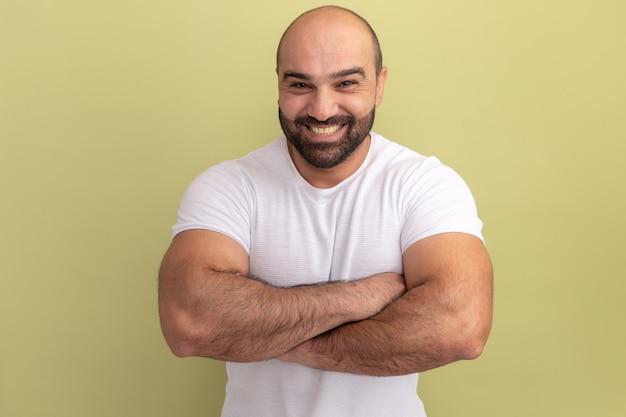 팔을 가진 얼굴에 미소를 지닌 흰색 티셔츠에 수염 난 남자가 녹색 벽 위에 서 교차