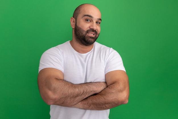 Бородатый мужчина в белой футболке с улыбкой на лице со скрещенными руками стоит над зеленой стеной