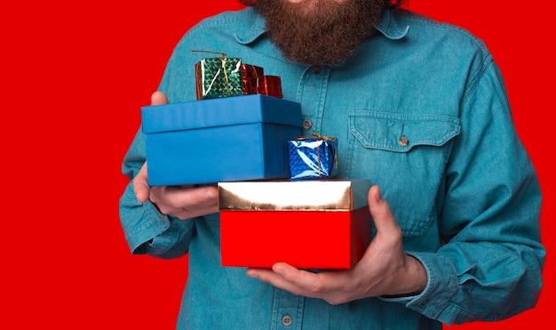 ひげを生やした男は、赤い背景の上にギフトボックスのスタックを保持しています。
