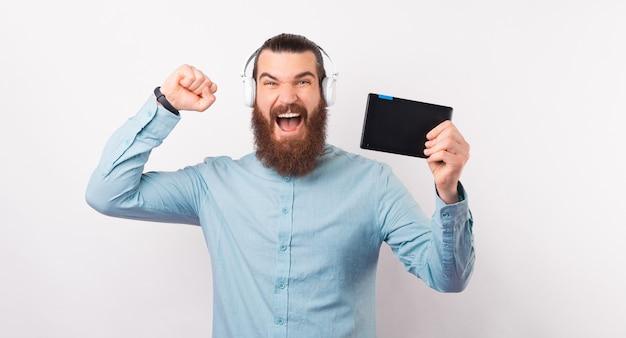 ひげを生やした男がタブレットを持っており、イヤホンを身に着けていると勝利を祝います。