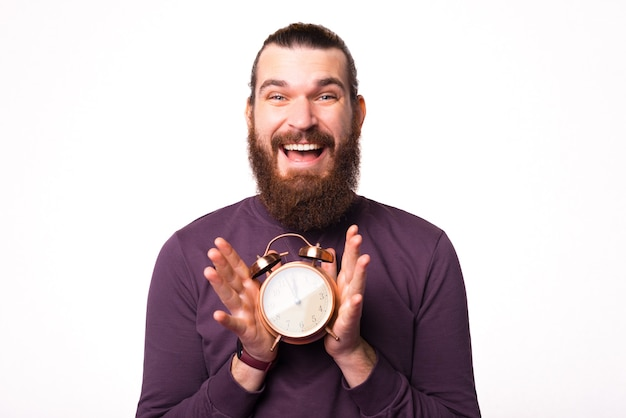 Bearded man is holding a clock with both hands smiling is looking at the camera