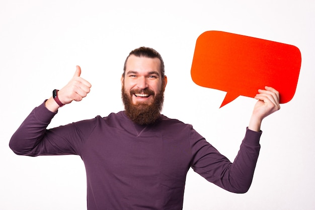 Bearded man is holding a speech bubble and smiling is showing a thumb up