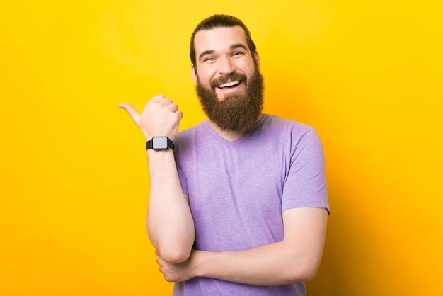 あごひげを生やした男は、黄色の背景に親指を脇に置いて示しています。