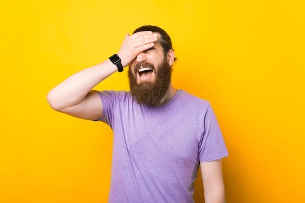 Бородатый мужчина делает лицо ладонью в студии на желтом фоне.