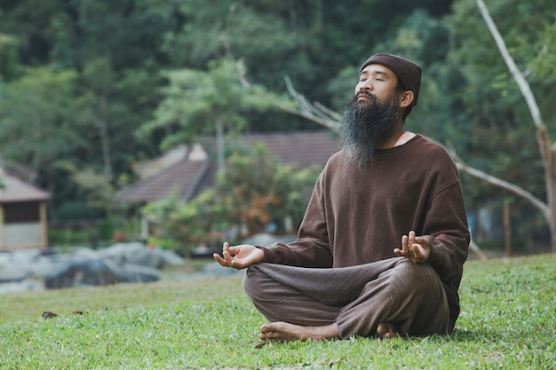 A bearded man is meditating on green grass