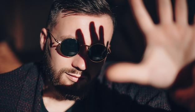 수염 난 남자는 손바닥으로 얼굴을 따뜻하게하는 태양 빛을 가리려고하는 동안 안경으로 포즈를 취하고 있습니다.