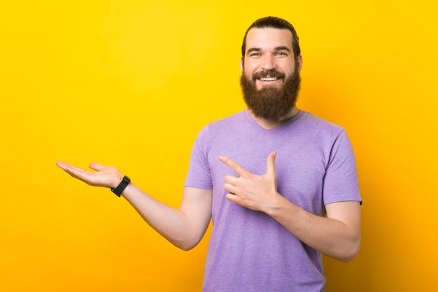 あごひげを生やした男は、黄色の背景に何かを提示しています。
