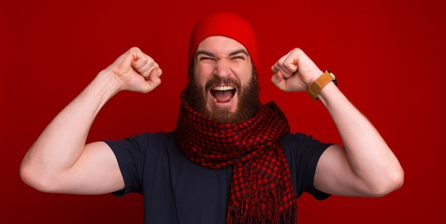 Bearded man is screaming with his hands up near red wall.
