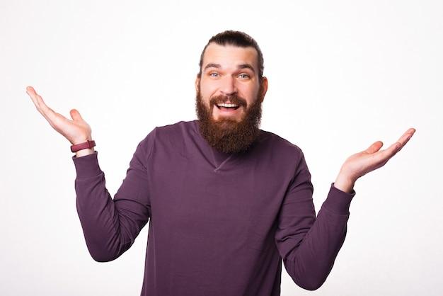 あごひげを生やした男は白い壁の近くに驚いた顔で知らないジェスチャーを示しています