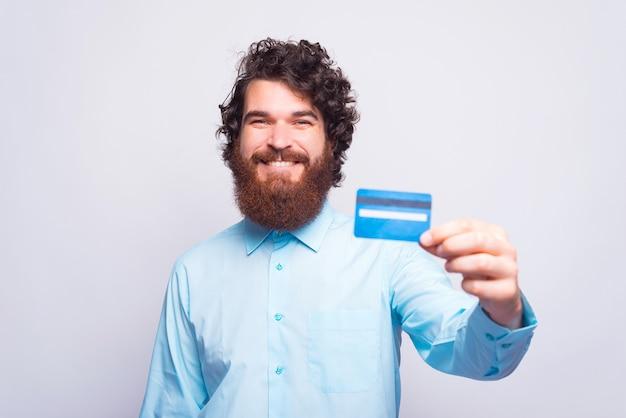 ひげを生やした男は笑顔でクレジットカードを持っています