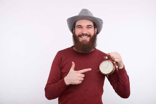 Bearded man is smiling at the camera with a hat on his head and holds a clock pointing at it.