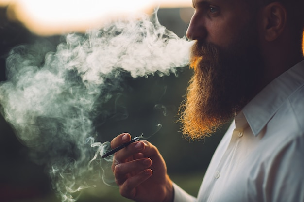 A bearded man is smoking a cigarette against the sunset.