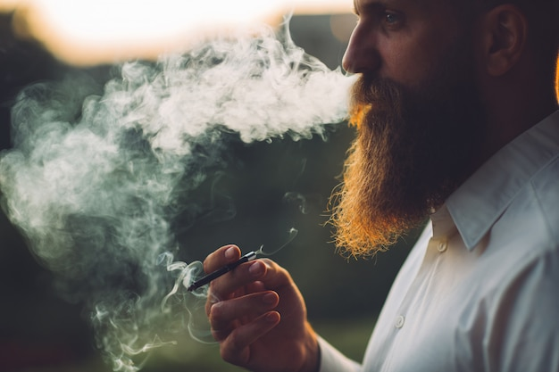 A bearded man is smoking a cigarette against the sunset