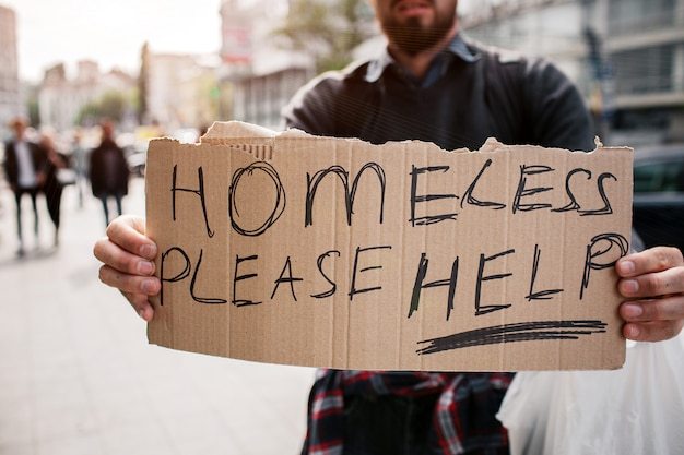 Bearded man is standing on street and holding a cardboard. it says homeless please help. guy is looking for some mercy from other people and help as well.