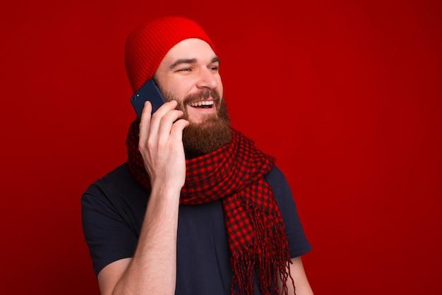 ひげを生やした男が電話に話していると、笑顔で、赤い背景に目をそらしています。