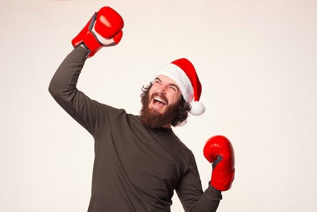 수염 난 남자는 크리스마스 경쟁에서 우승자입니다. 승리 제스처.