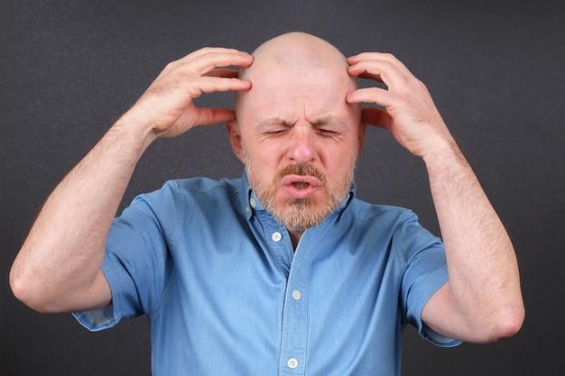 Бородатый мужчина очень эмоционально напряжен, держа руки возле головы