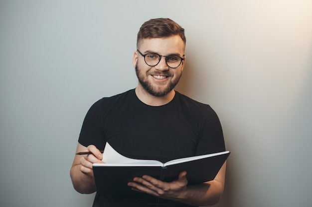 Bearded man is wearing glasses while holding a book and smile at camera on a gray studio wall