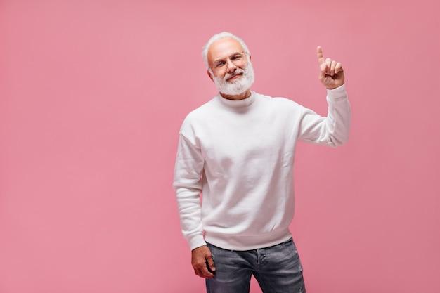 Uomo barbuto in jeans e maglione rivolto verso l'alto sul muro rosa