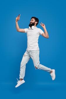 Бородатый мужчина прыгает и делает селфи