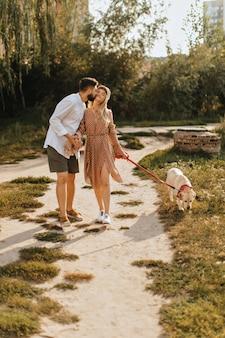Бородатый мужчина целует свою девушку в щеку, держа ее за руку. пара гуляет с лабрадором в саду.