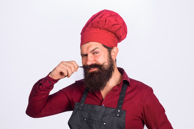 Bearded man in kitchen apron chief cook and professional culinary male cook in chef hat chef cook or