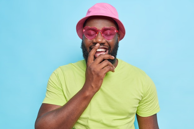 Bearded man laughs happily shows white perfect teeth keeps eyes closed wears pink panama heart shaped sunglasses casual green t shirt expresses positive emotions isolated on blue studio wall