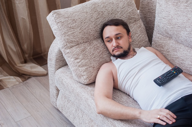 Bearded man lies on the couch with remote