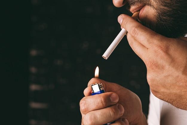 Bearded man lighting cigarette with fire lighter