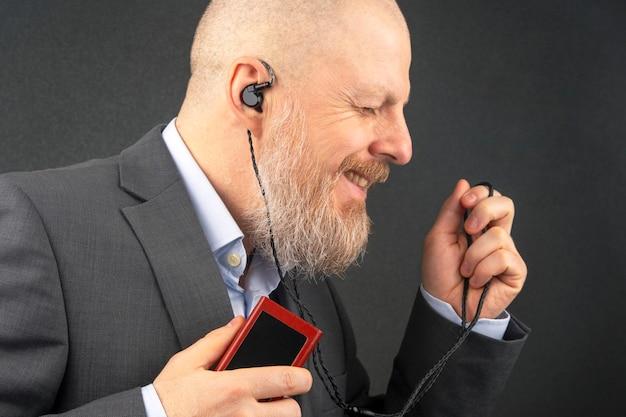 あごひげを生やした男性は、自宅で小さなヘッドホンのオーディオプレーヤーを使ってお気に入りの音楽を聴くのが好きです。