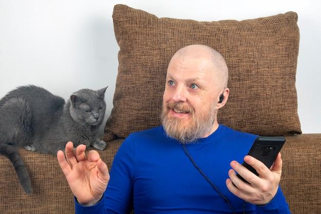 Бородатый мужчина с удовольствием слушает дома свою любимую музыку из телефона в небольших наушниках.