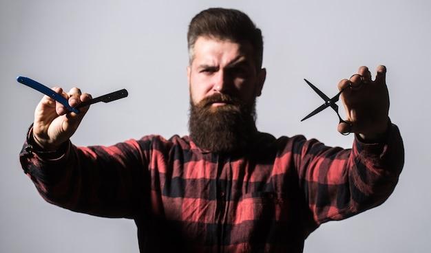 Бородатый мужчина, длинная борода, брутальный, кавказский хипстер с усами. парикмахерские ножницы и опасная бритва, парикмахерская. мужчина в парикмахерской. мужская стрижка в парикмахерской. мужская стрижка, бритье.