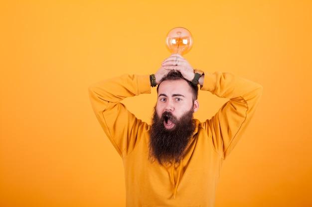 黄色の背景の前で彼の頭の上の電球に驚いて見えるひげを生やした男。イケメン。自信のある人。