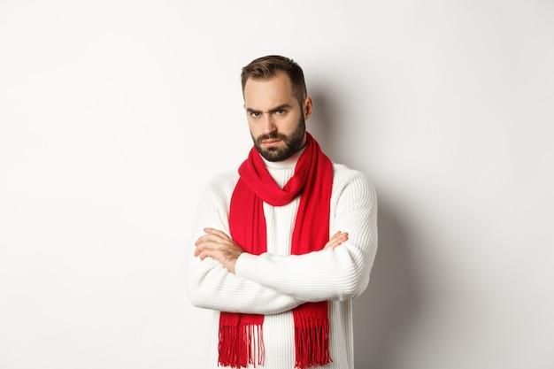 怒ってあなたに腹を立てているひげを生やした男は、防御的なポーズで胸に腕を組んで、白い背景の上にクリスマスセーターに立っている間やめなさい。