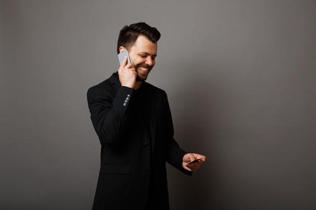 Бородатый мужчина смотрит на кредитные карты и разговаривает по телефону