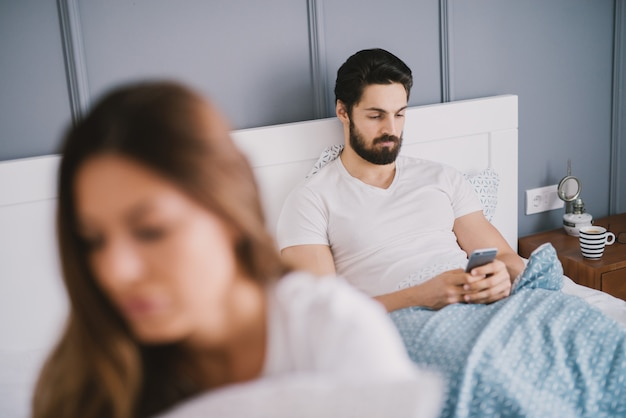 Bearded man looking at his phone while lying in bed with a young woman with brown hair.