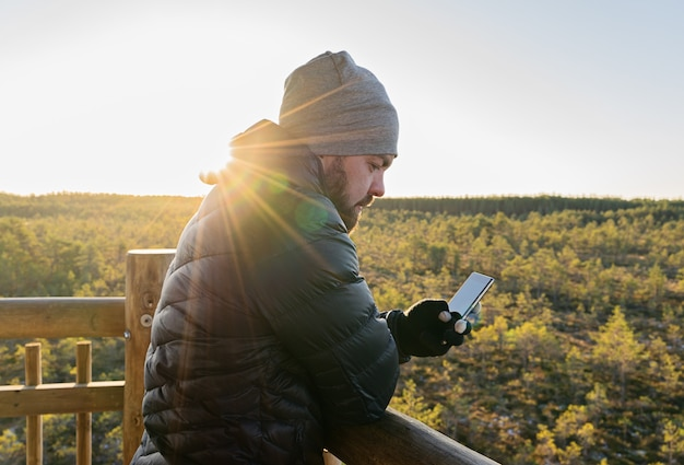 Bearded man looking at smartphone against forest