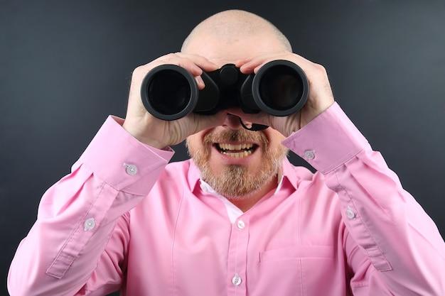 어둠 속에서 쌍안경을 통해 찾고 수염 된 남자