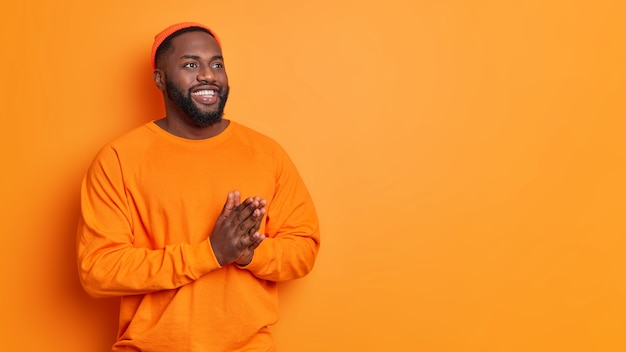 Bearded man looks thoughtfully aside keeps palms pressed together hopes for something good smiles gently wears hat and sweater poses against vivid orange wall copy space