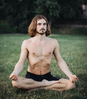 Bearded man in lotus pose sitting on green grass, concept of calm and meditation,