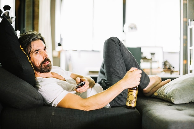 Bearded man lounging with beer on coach