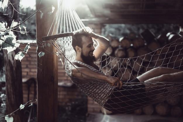 Uomo barbuto sdraiato amaca in una calda giornata estiva