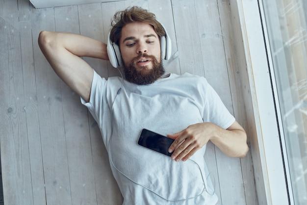Bearded man lying on the windowsill wearing headphones fun