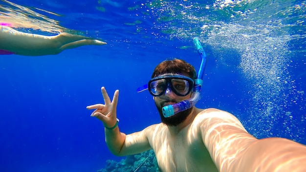 A bearded man in a mask and a breathing tube dives into the red sea against the background of a girl swimming behind him