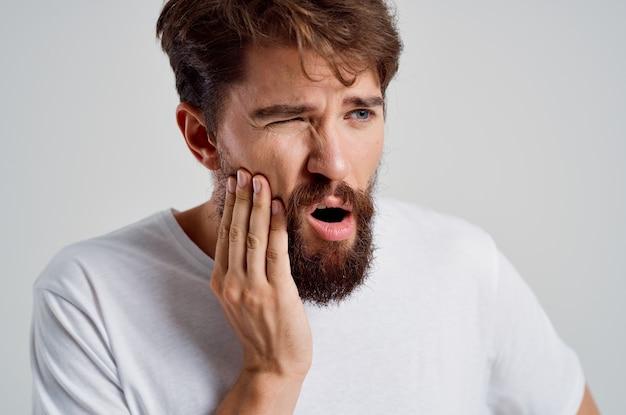 Бородатый мужчина медицина зубная боль и проблемы со здоровьем светлый фон