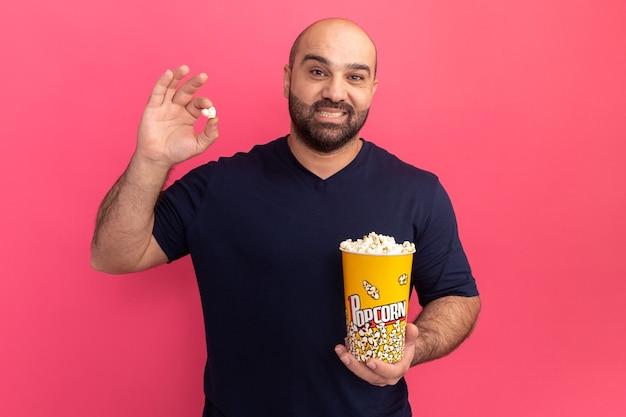 Uomo barbuto nel secchio della maglietta blu scuro con popcorn con il sorriso sul viso che tiene in piedi sopra il muro rosa